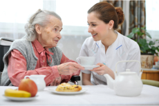 A caregiver giving an elderly a cup of tea
