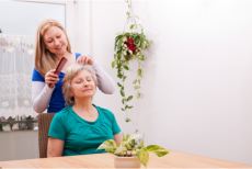 A caregiver combing the hair of an elderly