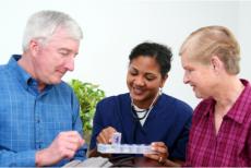A caregiver giving medicine to elders