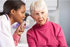 A nurse checking the ear of an elderly